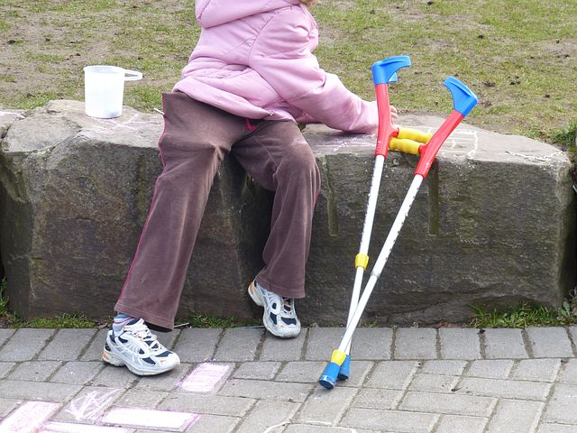 An older woman sitting on a rock neck to her crutches.