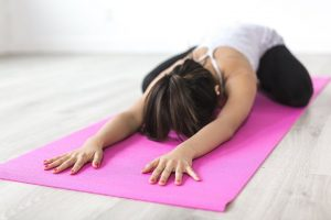 Young woman kneeling on a pink yoga mat doing a forward stretch for her back