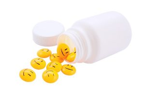 White prescription bottle with little yellow smiley face capsules spilling out.